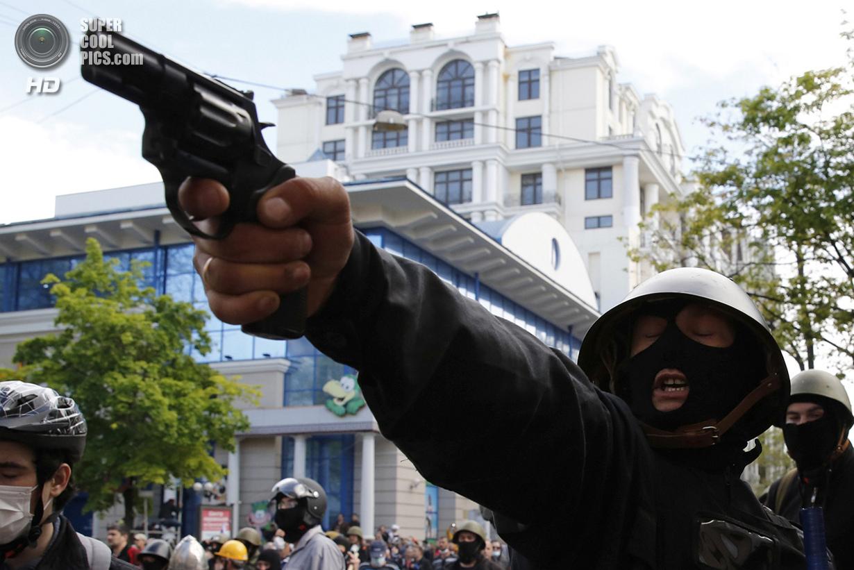 Украина. Одесса. 2 мая. Мужчина в каске стреляет из револьвера. (Reuters/Yevgeny Volokin)