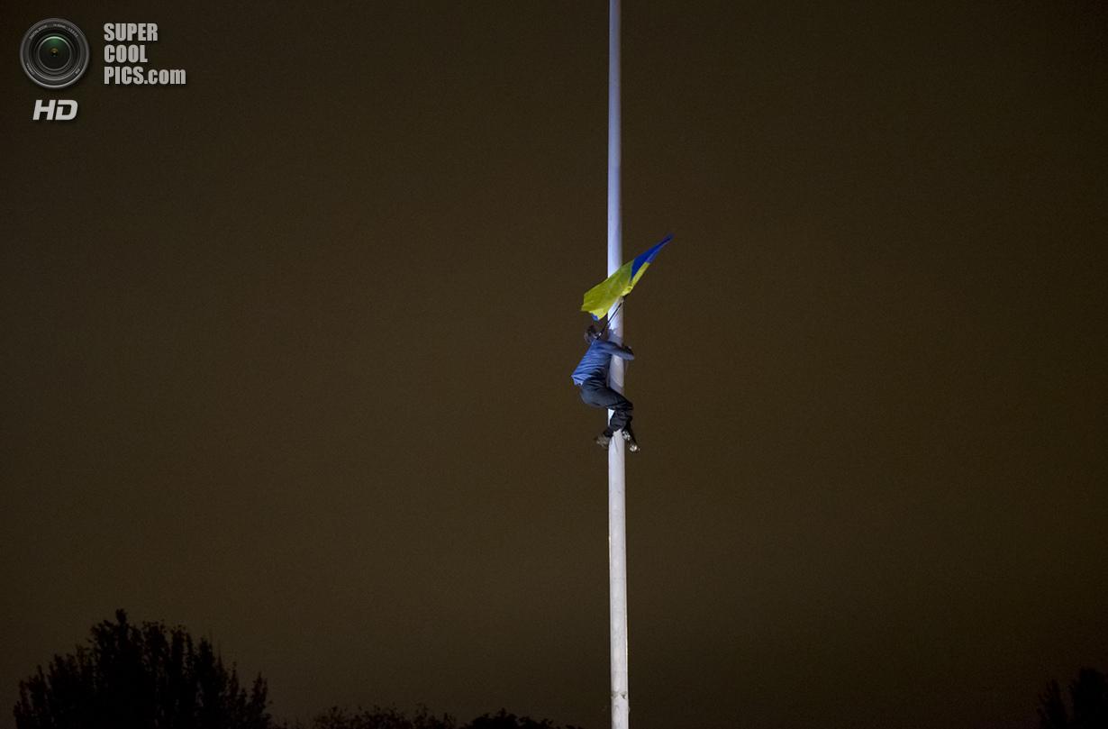 Украина. Одесса. 4 мая. Мужчина взбирается на флагшток, чтобы повесить национальный флаг Украины. (AP Photo/Vadim Ghirda)