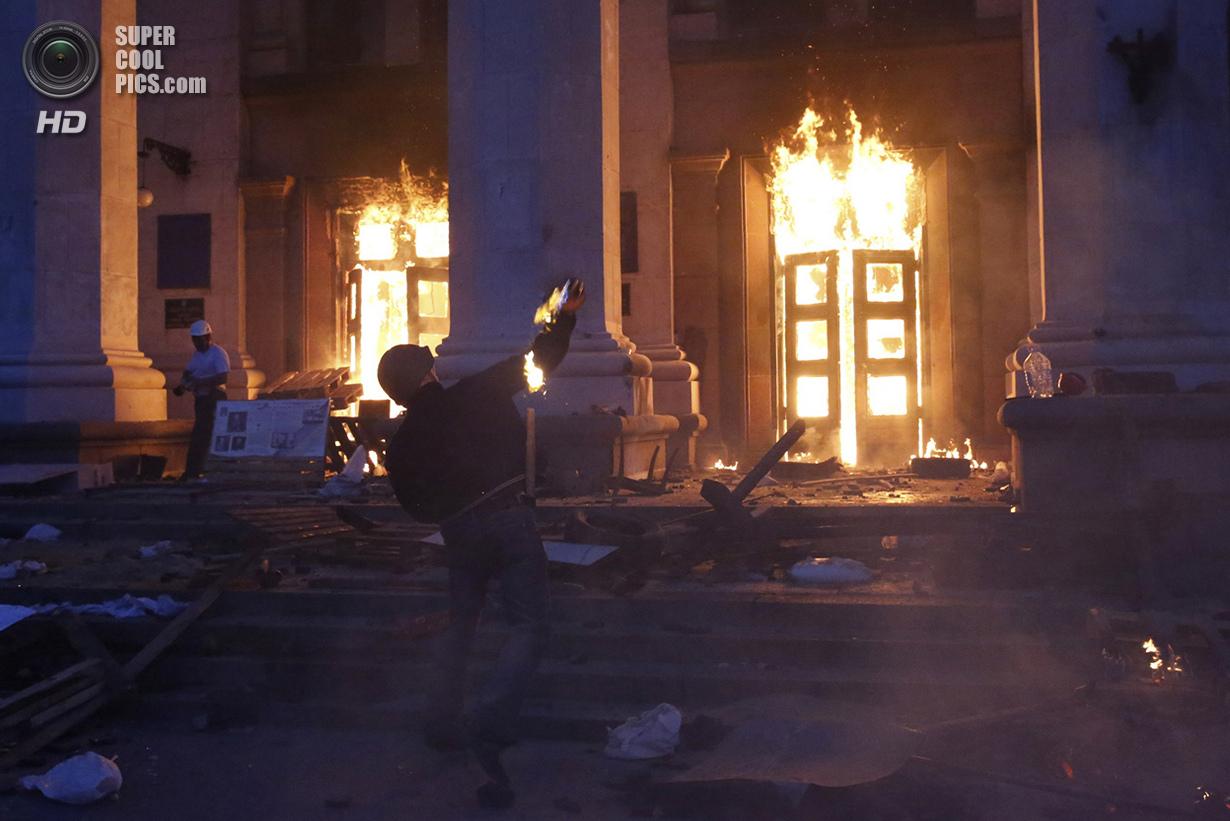 Украина. Одесса. 2 мая. Мужчина бросает коктейль Молотова в двери Дома профсоюзов. (Reuters/Yevgeny Volokin)
