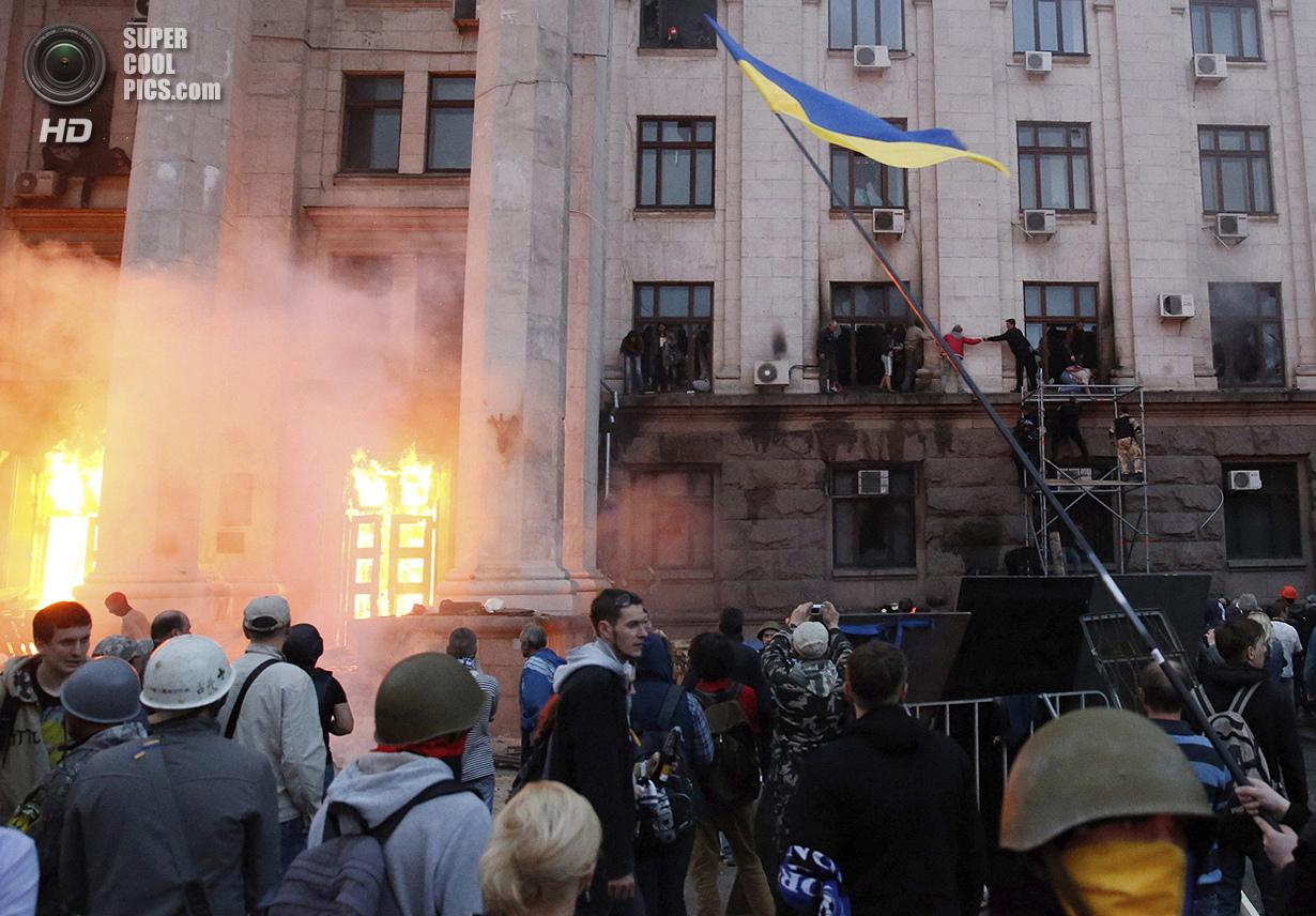Украина. Одесса. 2 мая. Оказавшись заблокированными в горящем Доме профсоюзов, люди пытаются выбраться через второй этаж. (Reuters/Yevgeny Volokin)